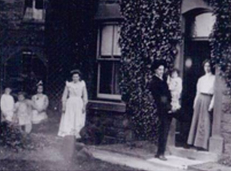 The Evans family at their home in England. Rice and Louise are standing at the door, holding Bergen. The older children are at far left. The girl in white is, I suppose, a maid.