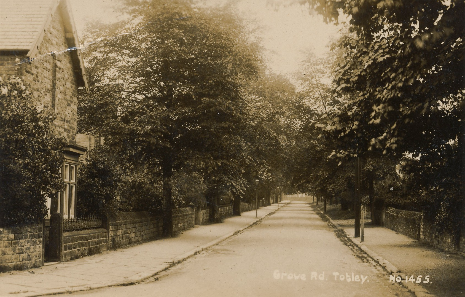 A tree lined Grove Road with gas lamps.